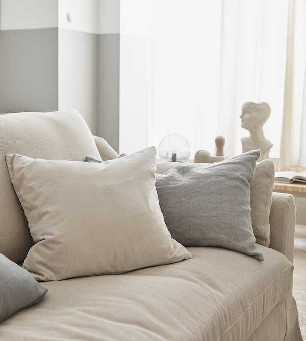 Neutral coloured pillows on a beige sofa in a bright living room.