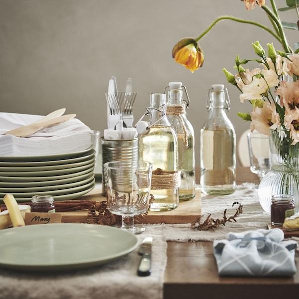 Neutral dining room setting, vase of flowers in the center. Light turquoise FÄRGKLAR plates.