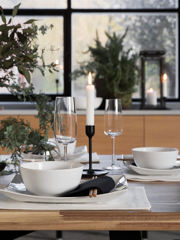 Neutral dinner setting with FLITIGHET bowl sitting on top of plate. Chopsticks folded in napkin beside with black candle stick as centerpiece