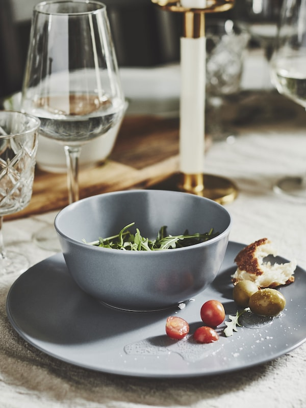 Neutral table saddle with salad in DINERA gray-blue bowl sitting on matching plate.