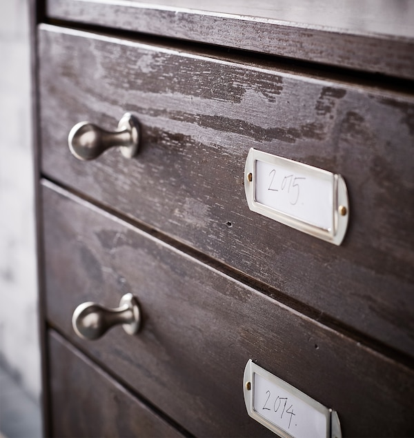 New metal knobs and label plates on an IKEA RAST 3 wooden drawer chest in stained dark brown.