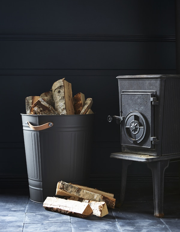 Next to a fireplace, a KNODD bin with leather handles holds firewood.