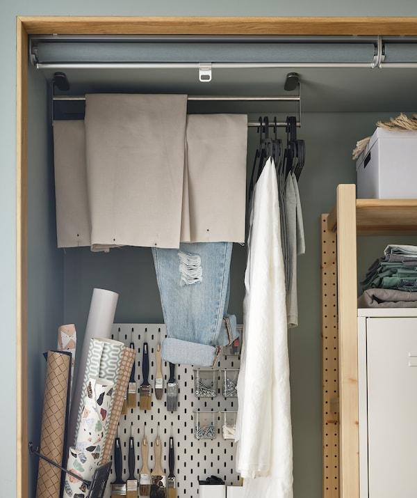 Niche indrettet til opbevaring af forskelligt hobbytilbehør: Hylder, hulplade og en håndklædestang, der er monteret i loftet med tekstiler på.