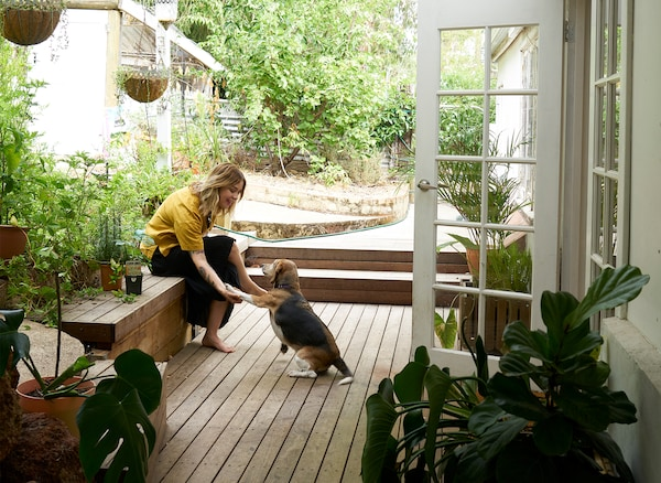 Nici and her dog sitting on wooden decking in a garden outside a white door.