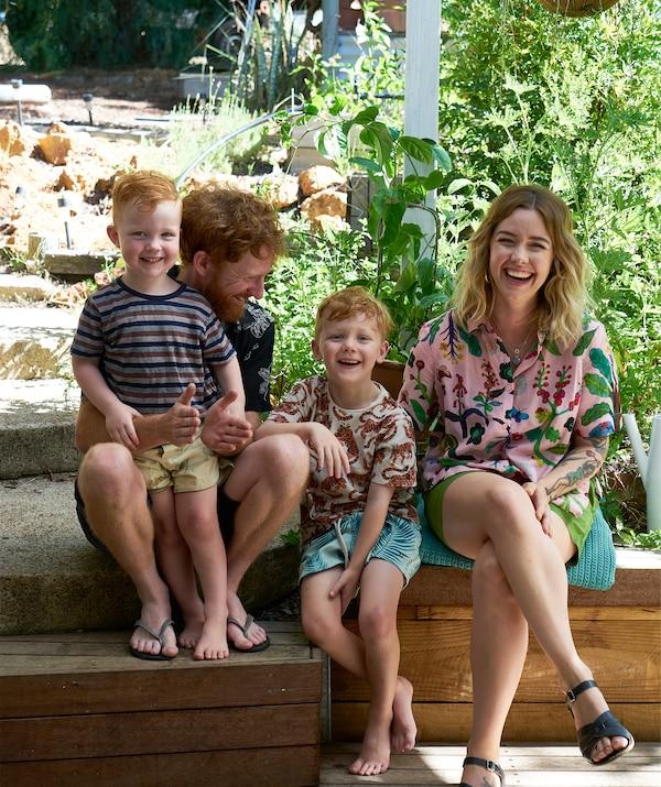 Nici, Ben e i loro due figli seduti su una panca in legno in giardino - IKEA