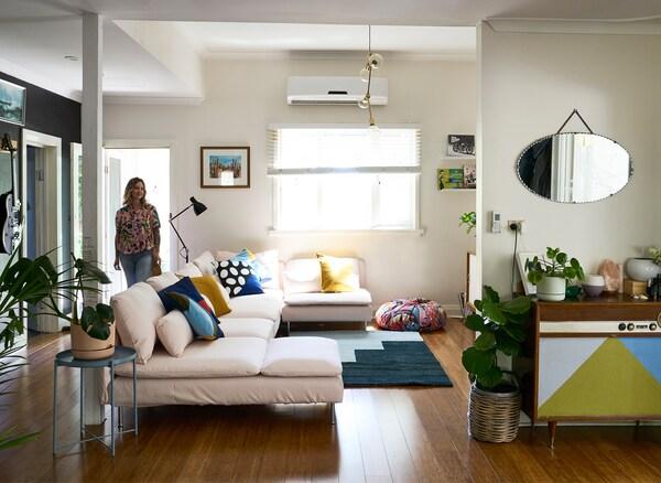 Nici entra in un soggiorno dalle pareti bianche con un divano rosa pallido, un tappeto blu e una credenza vintage - IKEA