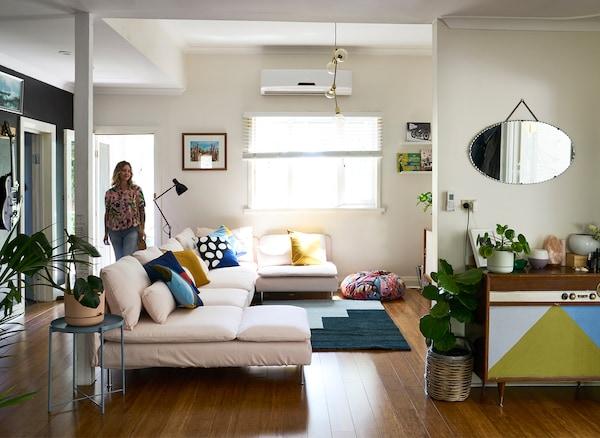 Nici kommt in ein weiss gestaltetes Wohnzimmer, u. a. mit SÖDERHAMN 4er-Sofa mit Récamiere + offenes Ende, Samsta hellrosa, Ebenfalls zu sehen sind ein blauer Teppich und ein Vintage-Sideboard.