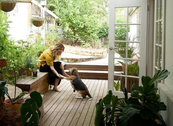 Nici seduta su una panca in giardino con il suo cane, davanti a una porta bianca - IKEA