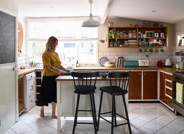 Nici standing at an island with two black bar stools, in a kitchen with brown cupboards, shelves and a large window.