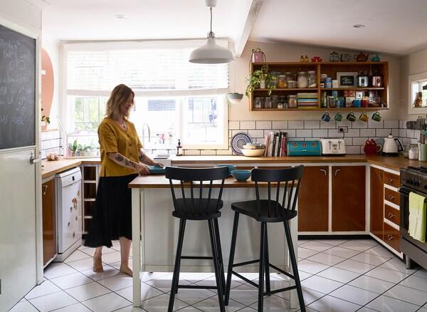 Nici steht an einer Kücheninsel, an der zwei NORRARYD Barhocker in Schwarz zu sehen sind. Hinter der Kücheninsel ist ein grosses Fenster zu sehen.