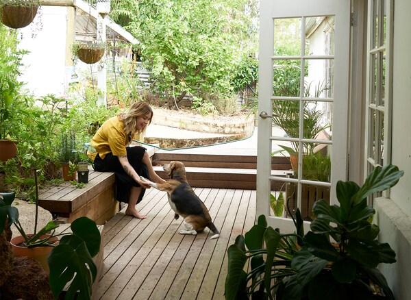 Nici und ihr Hund sitzen auf einer mit Holz bedeckten Terrasse, auf die eine weisse Tür führt.