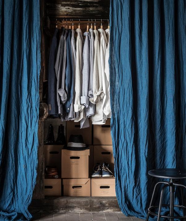 Niebieskie zasłony zawieszone przy wieszaku z koszulkami i pudełkami z butami.