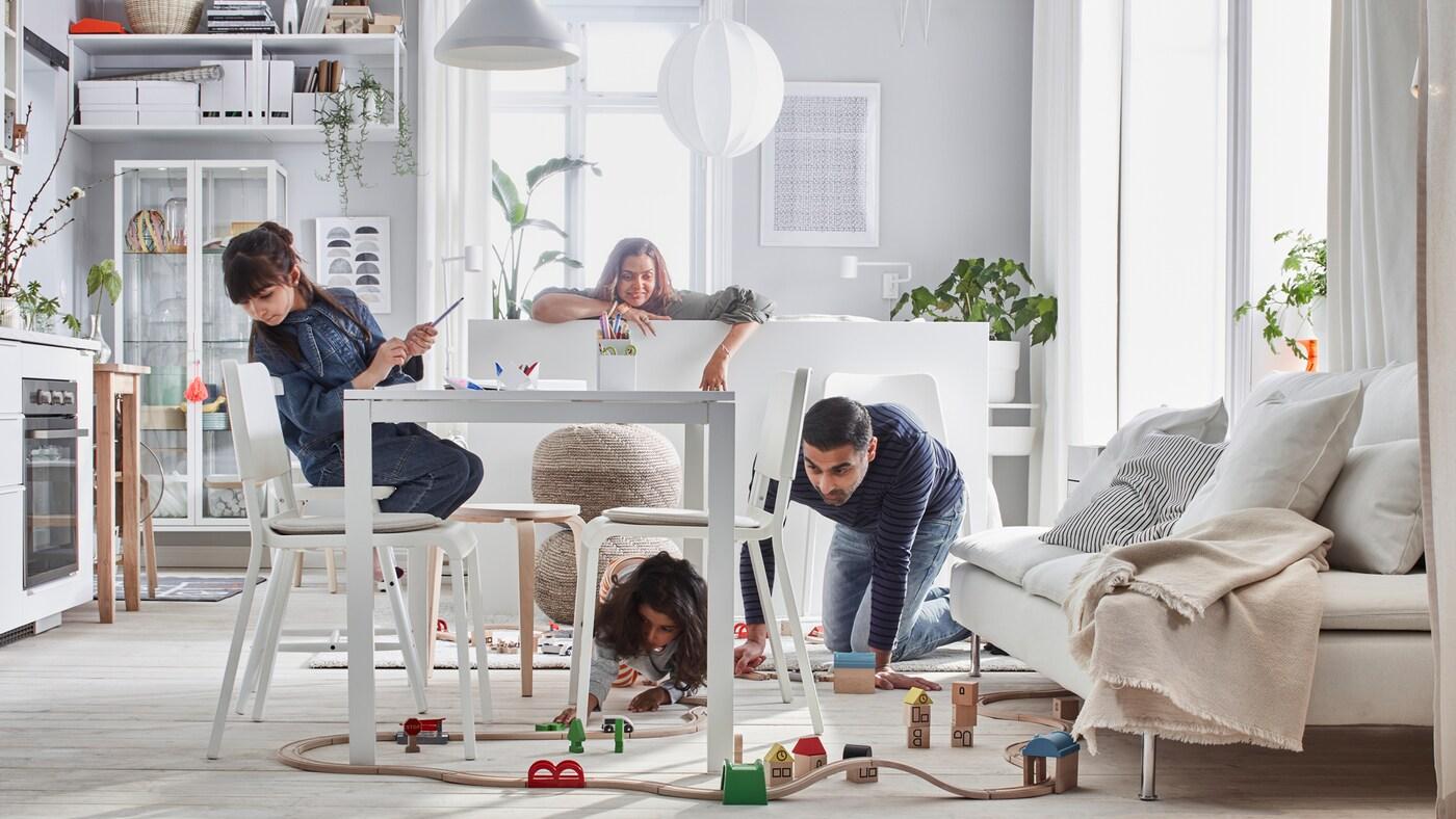 Nieduże mieszkanie, w którym cała rodzina bawi się drewnianą kolejką LILLABO rozłożoną w pomieszczeniu z łóżkiem, sofą, stołem, aneksem kuchennym i meblami do przechowywania.