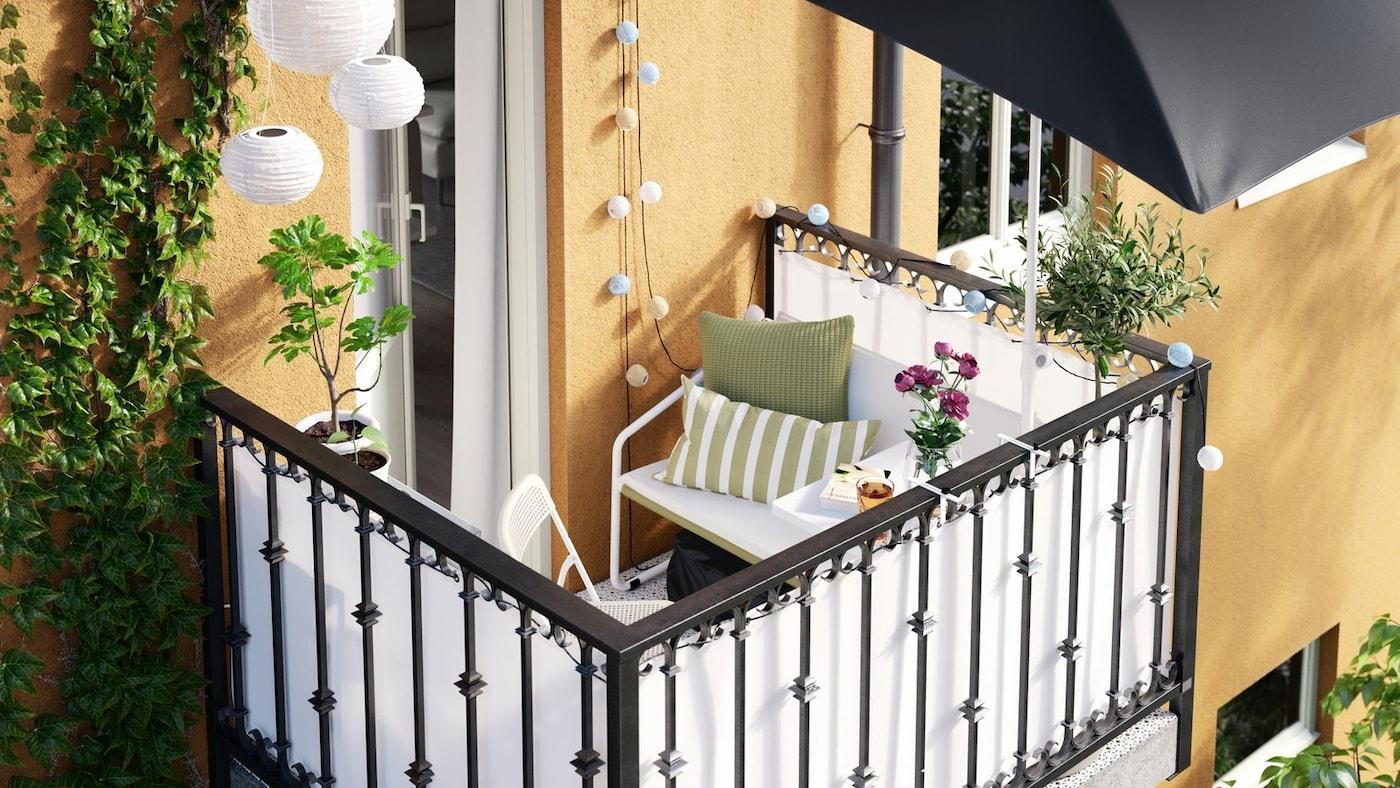 Niewielki balkon w pomalowanym na żółto budynku wielorodzinnym, a na nim biała sofa, łańcuchy świetlne i mały stolik zawieszony na balustradzie.