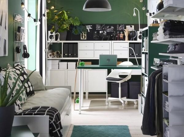 Niewielki, utrzymany w zielonej kolorystyce pokój z zielonym stołem, białymi regałami, leżanką, otwartą szafą i czarną lampą wiszącą.