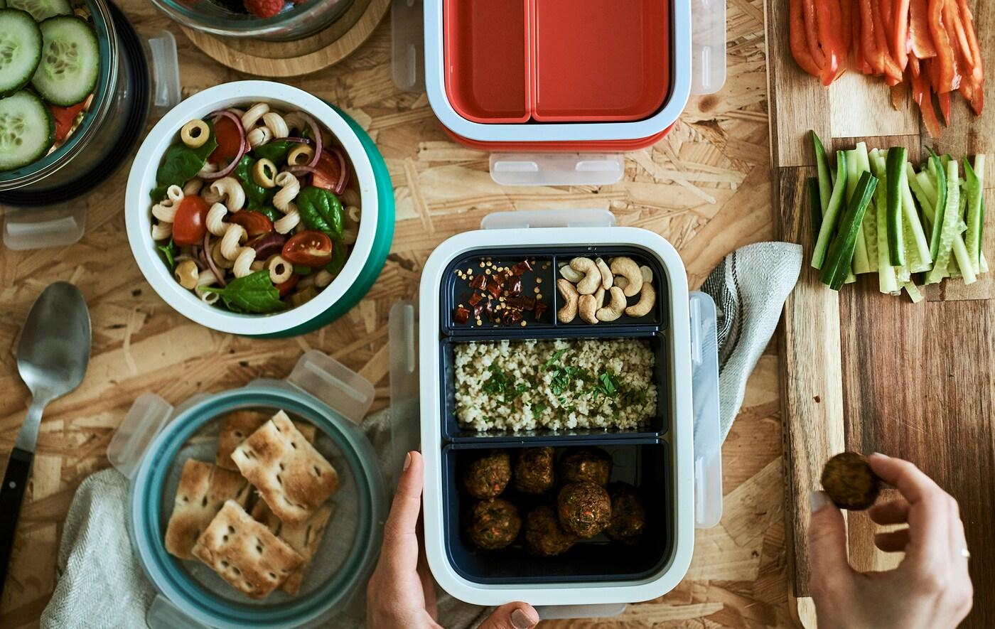 弁当箱に詰められた食べ物。1つには仕切りがあり、それぞれに異なる食べ物が入っています。丸形のプラスチック製タブにはパスタサラダが入っています。