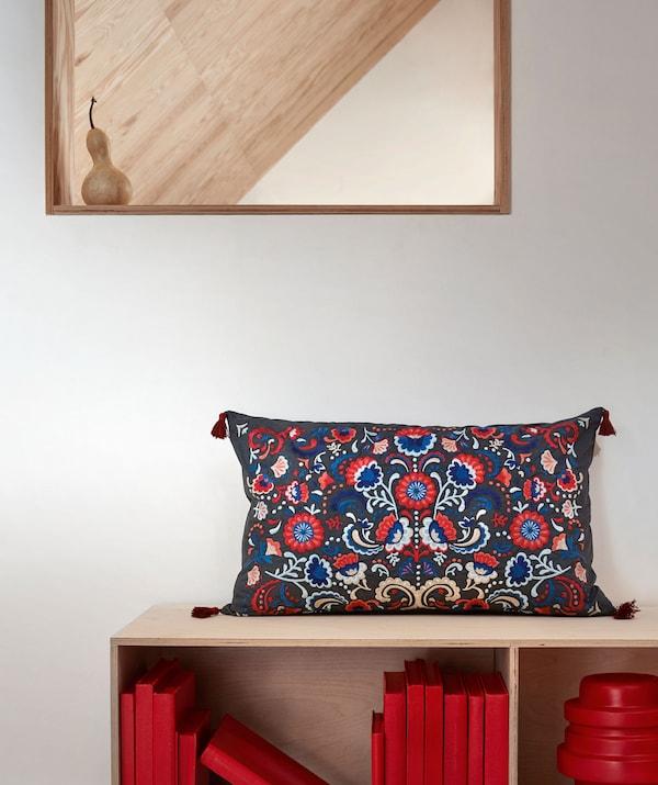 壁際にミラーと低い書棚を並べたセクション。カラフルな刺繍のクッションを上に置いて。