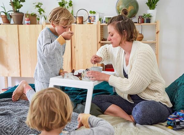 Nina et ses deux enfants en train de manger leur petit déjeuner au lit avec des armoires en bois à l'arrière-plan.