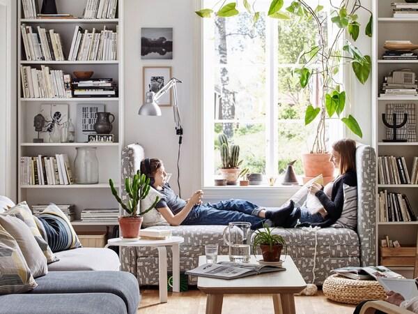 対になった白い書棚の間にあるモジュール式ソファユニットに向かい合って座っている2人の姉妹。