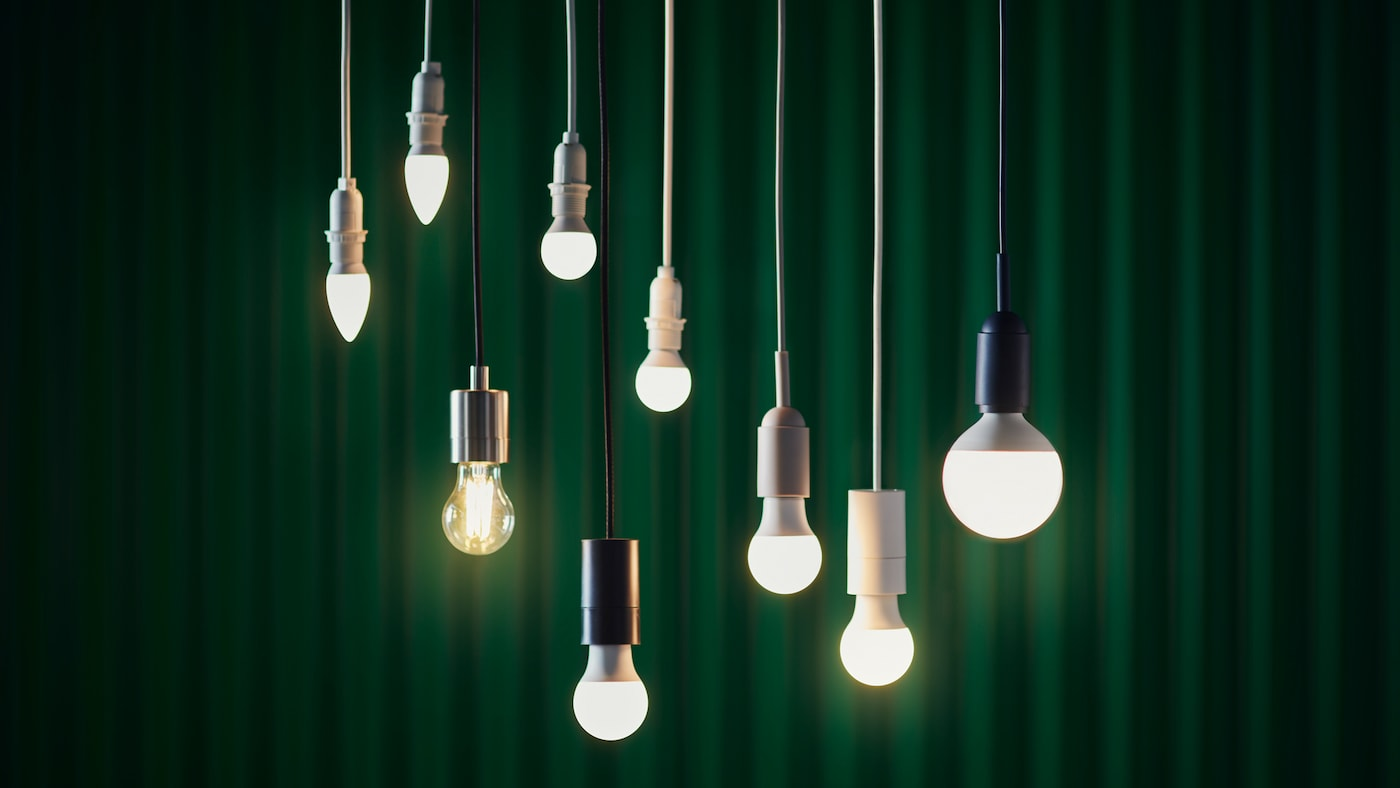 Nine SOLHETTA LED bulbs are hanging from the ceiling, in front of a green curtain.