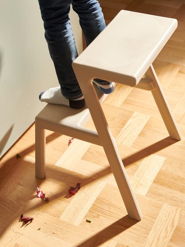 Niño de pie sobre un taburete MÄSTERBY, colocado al lado de una cocina. Trozos de cebolla roja en el suelo.