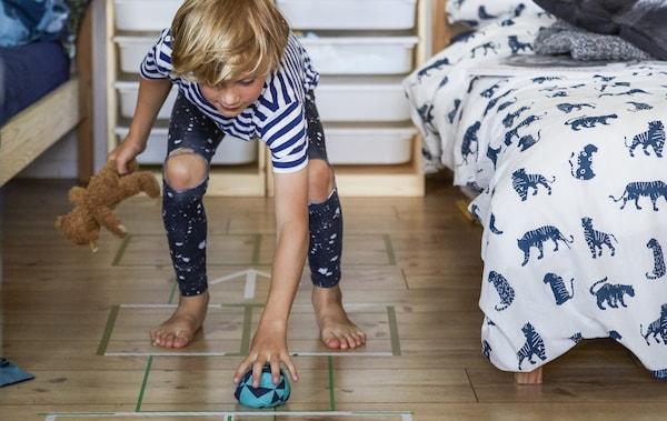Niño jugando a la rayuela en un suelo de madera entre dos camas.