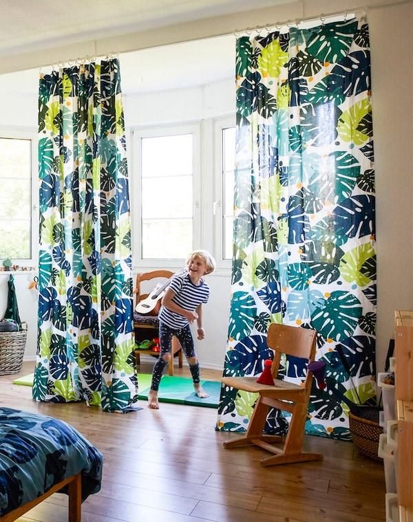 Niño jugando en un dormitorio grande con textiles con temática de jungla.