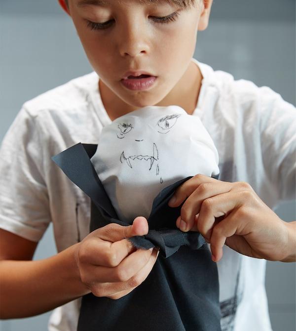 Niño pequeño atando una servilleta negra al muñeco de Drácula.