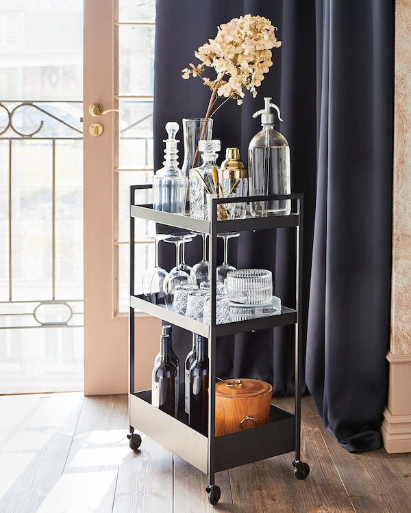NISSAFORS kolica u crnoj boji, na točkićima, s bocom za sodu, čašama, nekoliko boca i biljkom u staklenoj vazi.