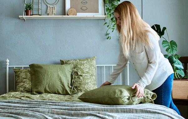 Nő a hálószobában, szürke és zöld dekorációval, növényekkel, párnákkal és zöld ágyneművel.