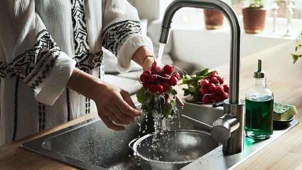 Nő áll a mosogató mellett és zöldséget mos a ÄLMAREN konyhai csapnál.