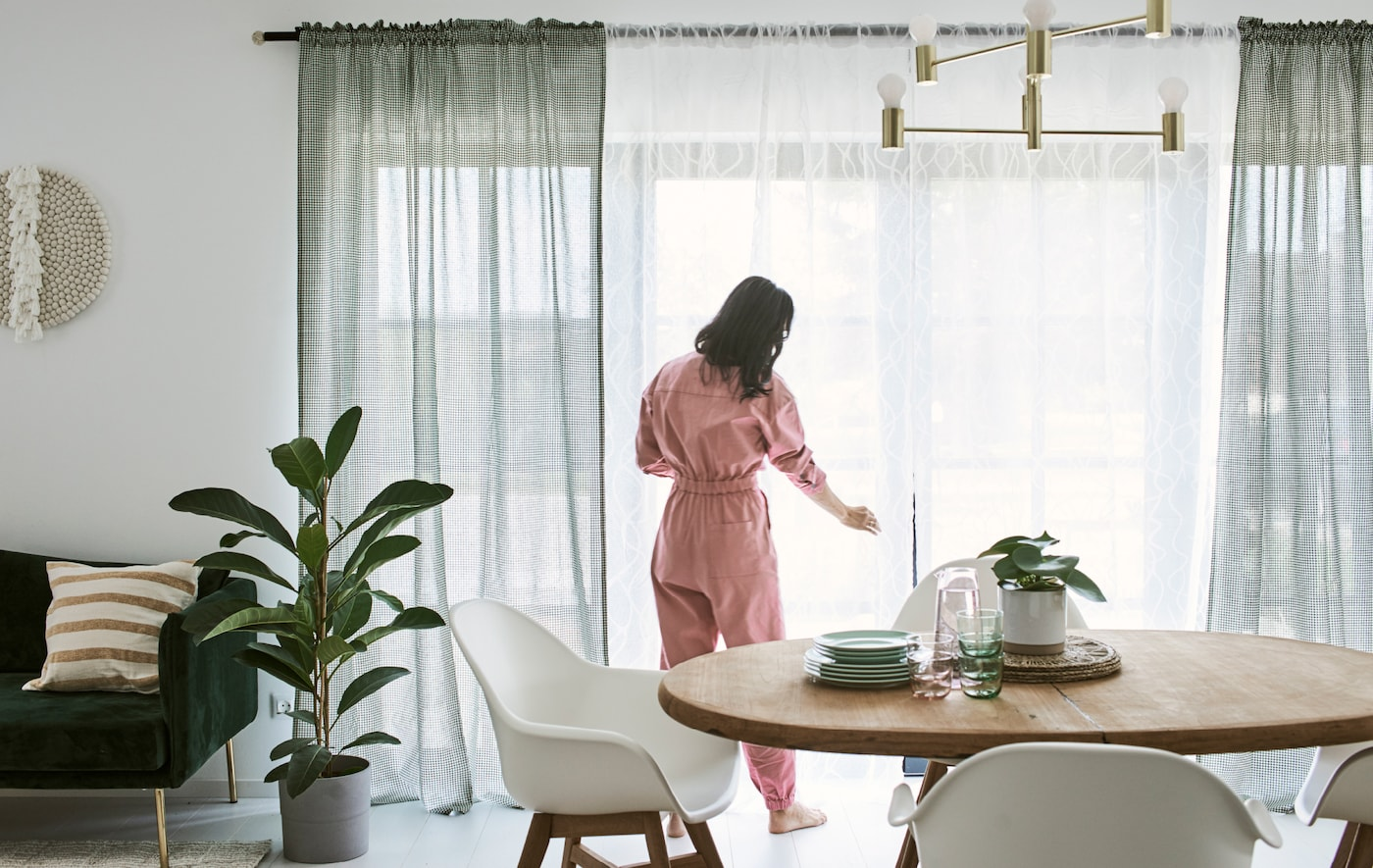 Nő, rózsaszín ruhában a függönyöket igazgatja egy étkezőben, fa étkezőasztallal és fehér székekkel.