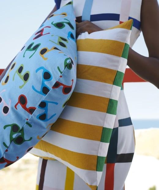 Nő, színes ruhában, napszemüveg mintás és csíkos díszpárnával.