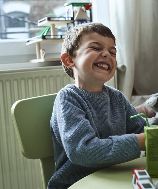 Noah ابن Amélie يجلس ضاحكًا على طاولة.