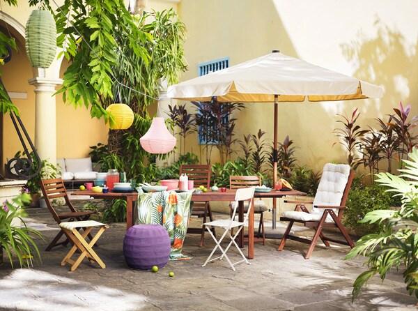 屋外のバルコニーに、屋外用チェア、鉢植えの植物がたくさんある。