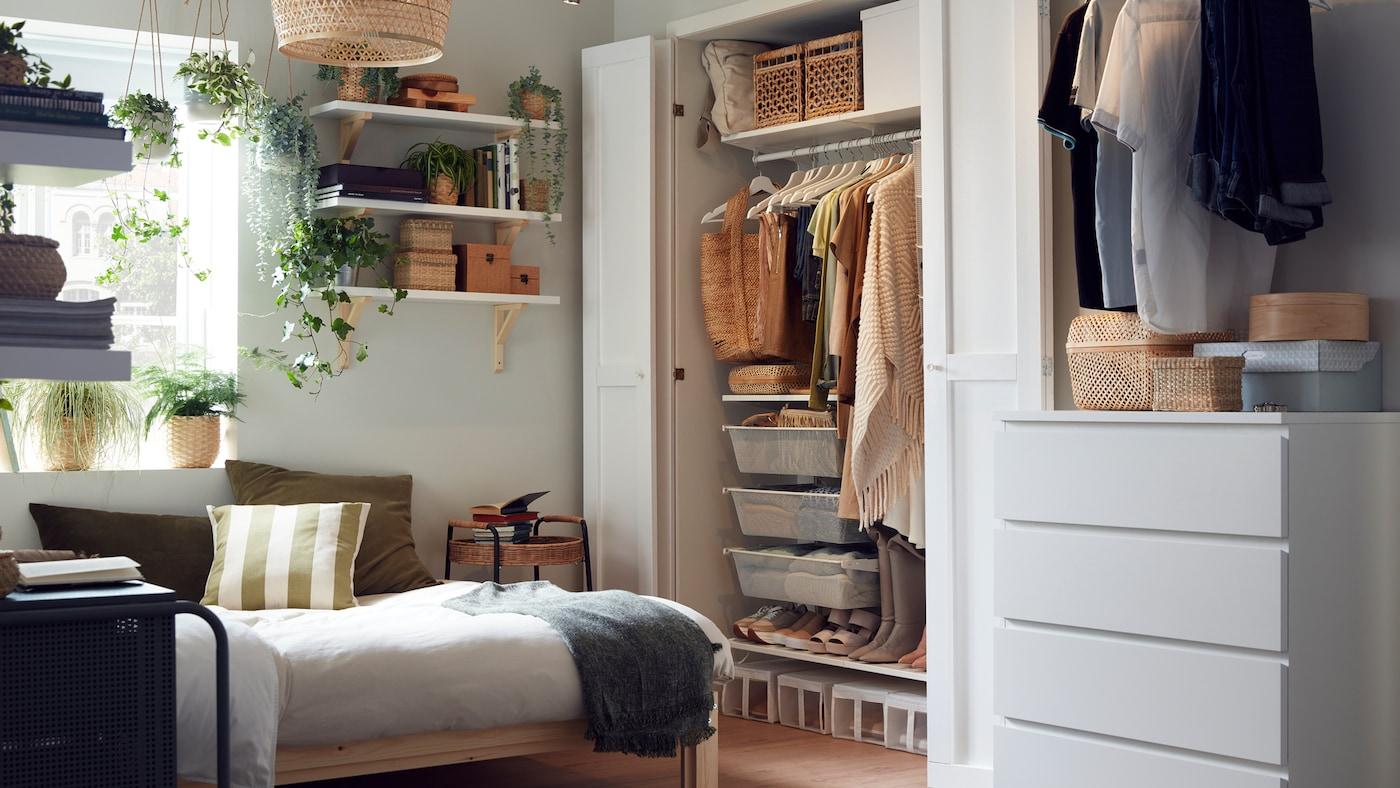 木製のベッドフレーム、衣類をきちんと整理整頓したワードローブシステム、ボックスや植物を置いた棚板がある小さなベッドルーム。