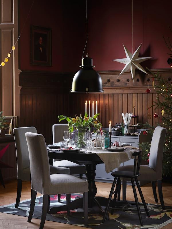 円形のブラックのINGATORP/インガートルプ テーブルに、相性のよいグレーのチェアを組み合わせ、華やかな花のディスプレイをセッティング。