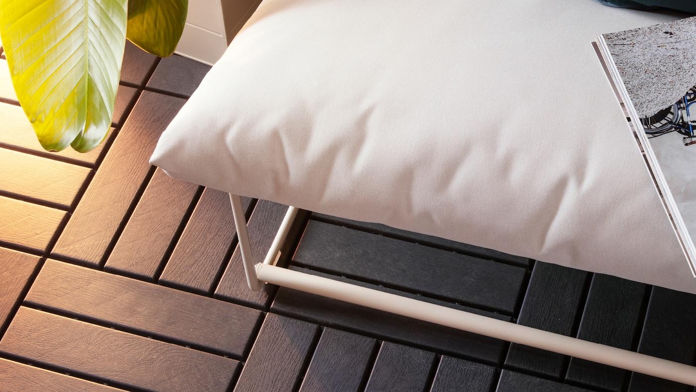 木目調の屋外用フローリング。白い布張りの屋外用ソファを配置し、その上には本が置かれている。