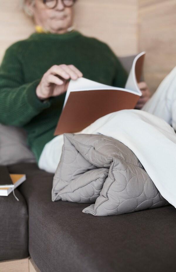 Noin 60-vuotias mies istuu seinään nojaten ja lukee kirjaa. OMTÄNKSAM-monitoimityyny on rullattu miehen polvien alle.