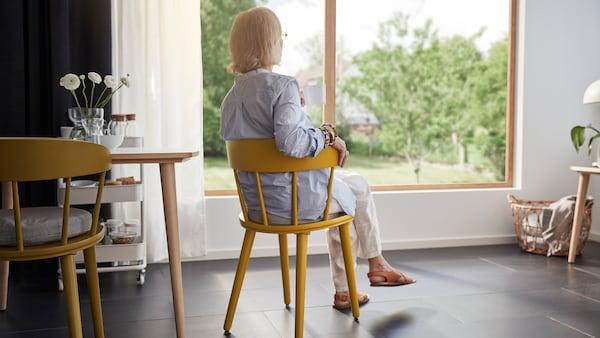 Noin kuusikymmenvuotias nainen istuu mukavasti keltaisessa OMTÄNKSAM-tuolissa. Nainen istuu selkä katsojaan päin ja katselee ulos suurista ikkunoista.