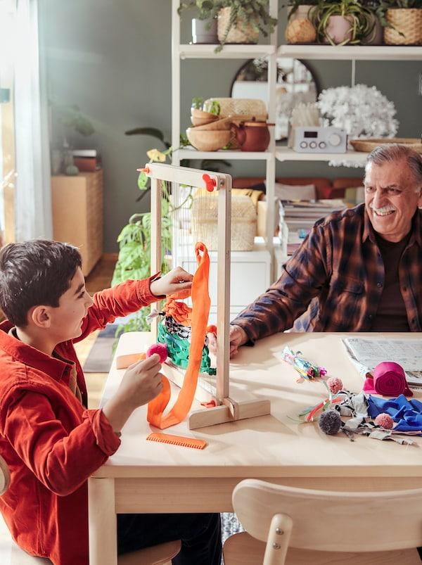Nonno e nipote seduti al tavolo, giocano insieme con un set telaio LUSTIGT.