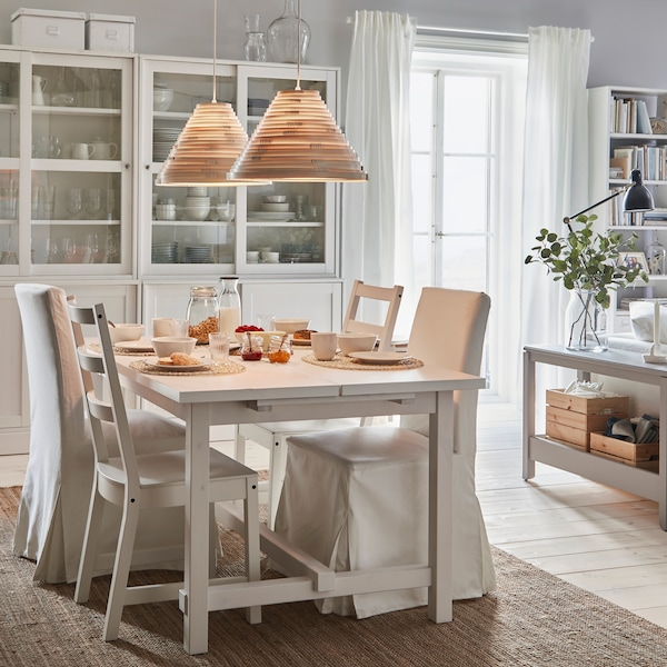 NORDVIKEN extendable table and chairs stand in a breakfast setting. A lit pendant lamp gives warm lighting from above.