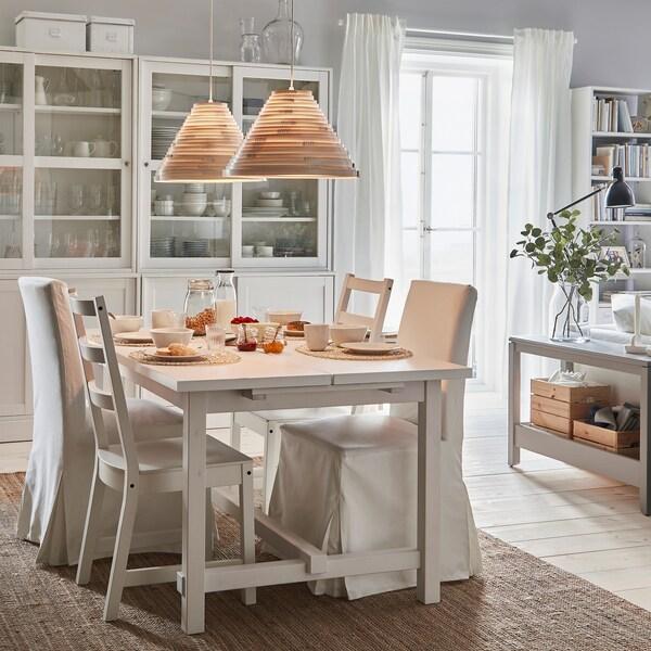 NORDVIKEN produživi sto i stolice, postavljeni za doručak. Upaljene visilice odaju toplo svetlo odozgo.