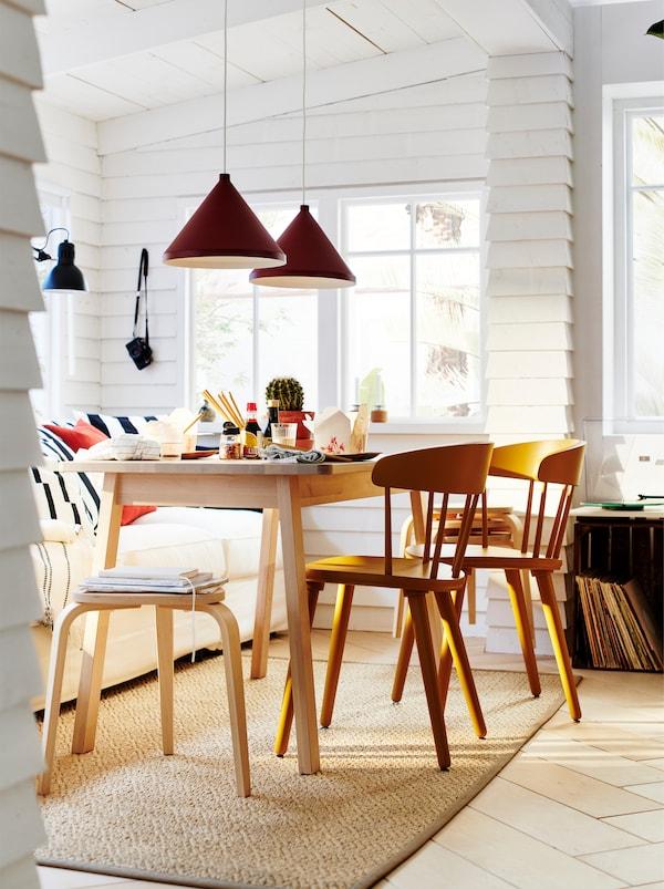 NORRÅKER sto okružen OMTÄNKSAM stolicama, za trpezarijski sto u beloj, osunčanoj sobi sa zidovima i drvenim gredama.