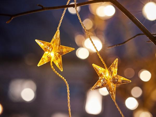 屋外のツリーにつり下げられた星形のゴールドのSTRÅLA/ストローラ LEDライトチェーンの星2個に焦点が合っている。