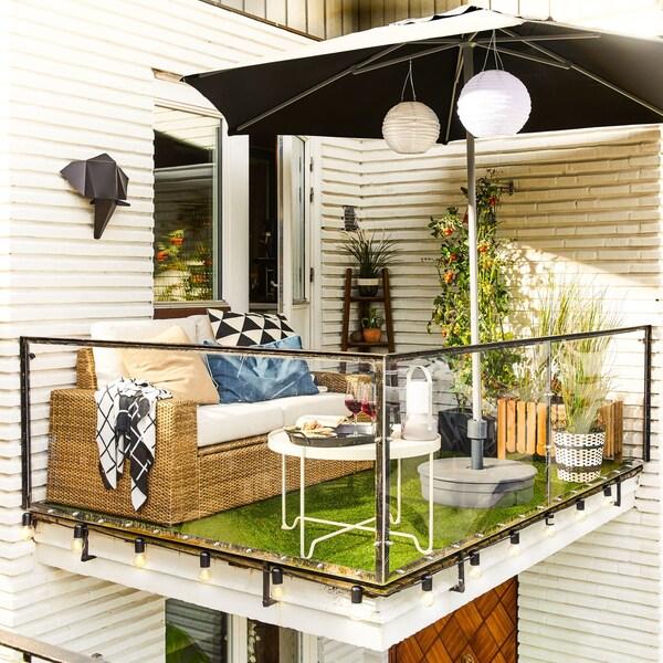 Nowoczesna, brązowa/beżowa, 2-osobowa sofa ogrodowa SOLLERÖN na małym balkonie z niskim stołem i parasolem.