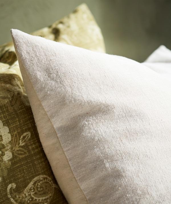 天然の綿を使用したベージュの枕のクローズアップ。隣にグリーンのペイズリー模様の枕。