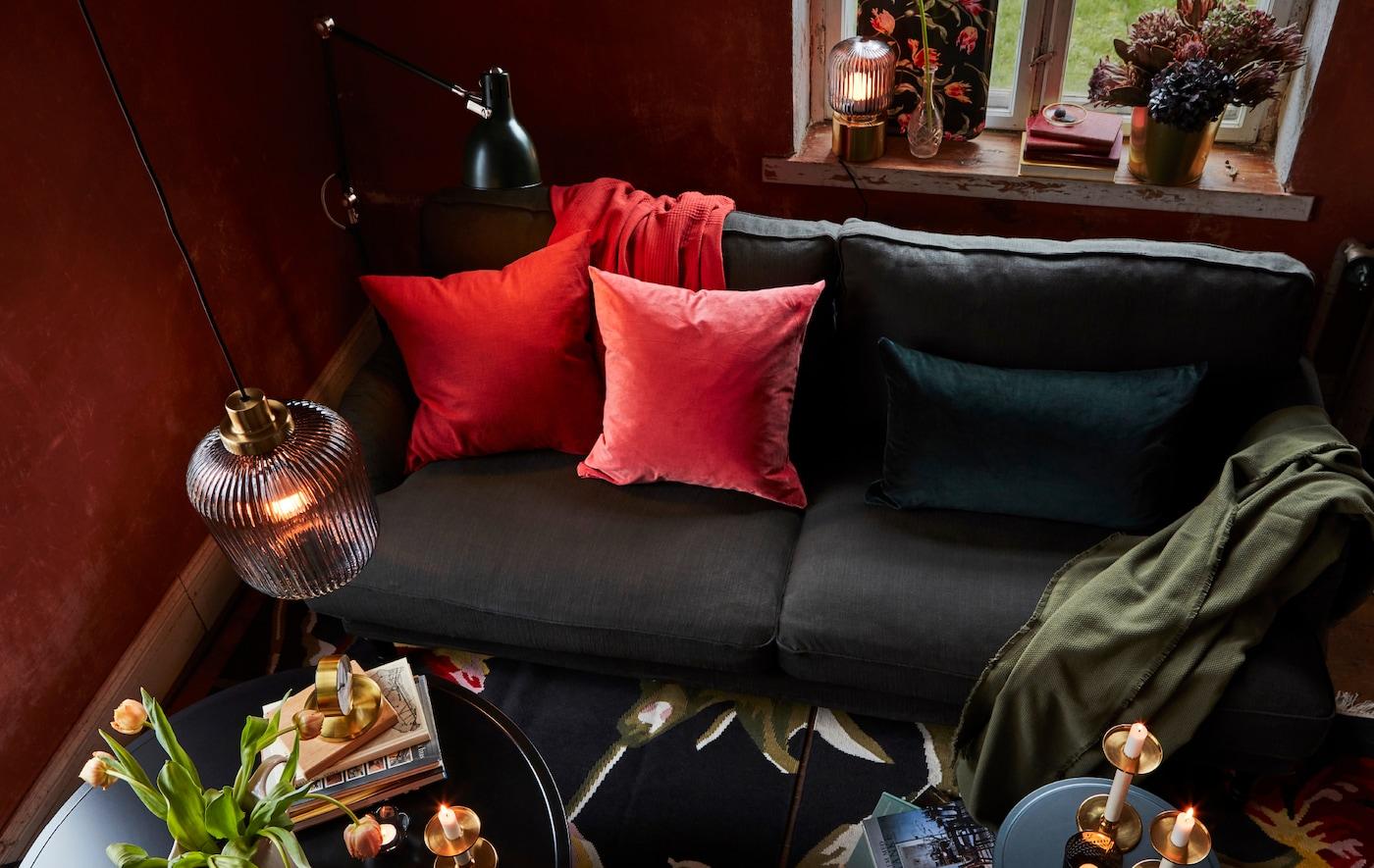 Numa sala, uma mistura de candeeiros suspensos, candeeiros de pé e de mesa e um sofá com almofadas coloridas ajudam a definir um ambiente quente e acolhedor.