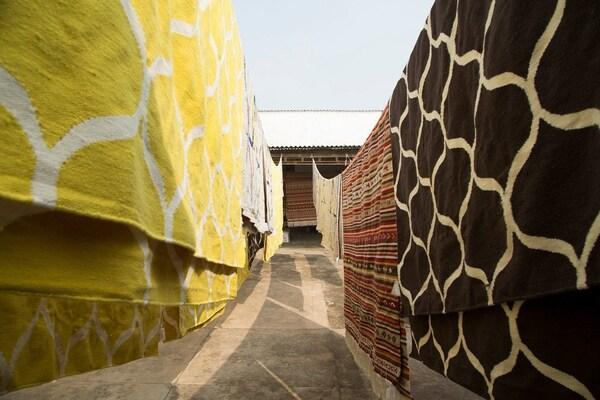 Numerosas alfombras colgadas al aire libre, con una alfombra plana hecha a mano STOCKHOLM de color amarillo con patrón de red.