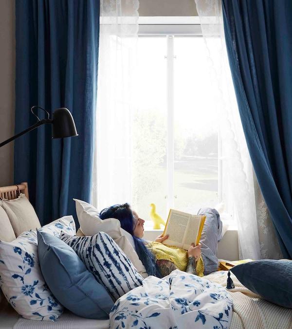 Nuori nainen lukee kirjaa ikkunan edessä sinisävyisessä makuuhuoneessa
